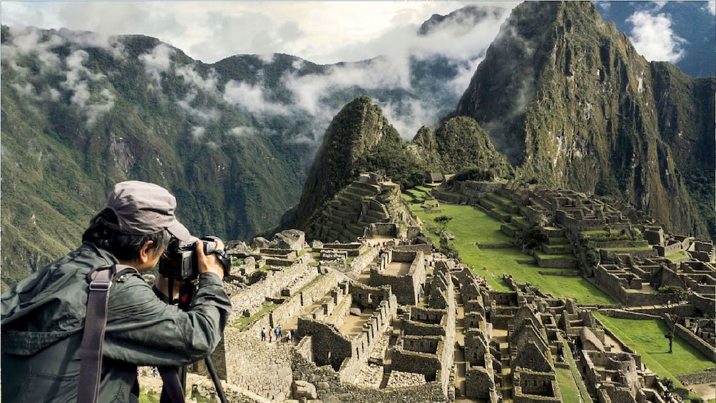 Show item 1 of 5. Man taking photograph of ruins of Machu Picchu