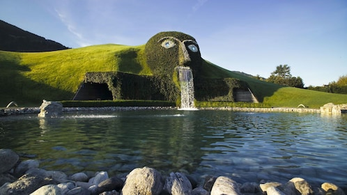 Large vegetation covered head with waterfall flowing from mouth into man made pond in Swarovski Kristallwelten in Innsbruck