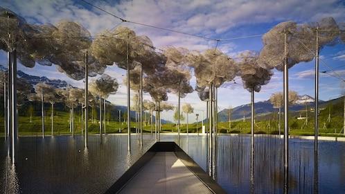 Large artwork suspended over man made pond in Swarovski Kristallwelten in Innsbruck