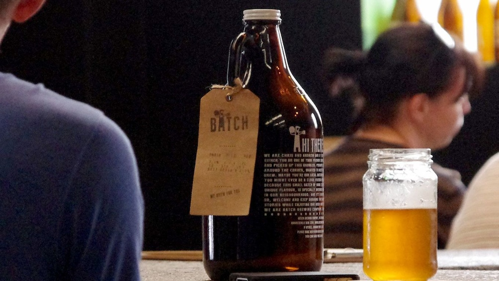 Show item 1 of 5. Growler and glass of beer at a bar in Sydney