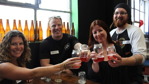 Group toasting with glasses of beer at a bar in Sydney