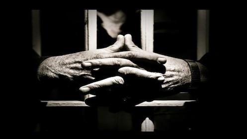 hands folded together through prison cell bars in Melbourne