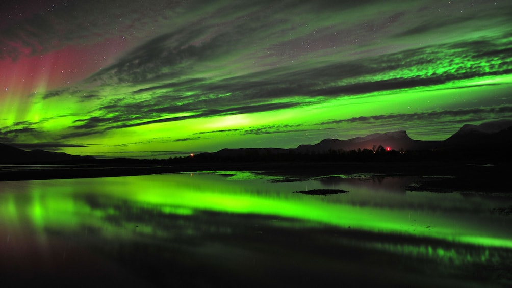 Åpne bilde 2 av 5. Streaks of green light up the night sky and are reflected in the lake below in Stockholm