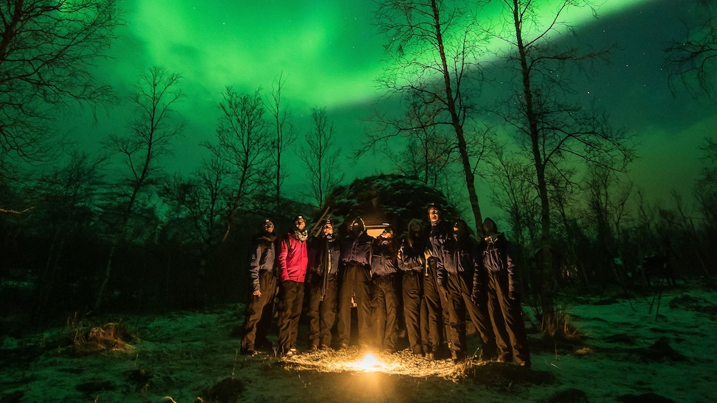 Åpne bilde 5 av 5. Group around a campfire with Northern Lights in the sky overhead