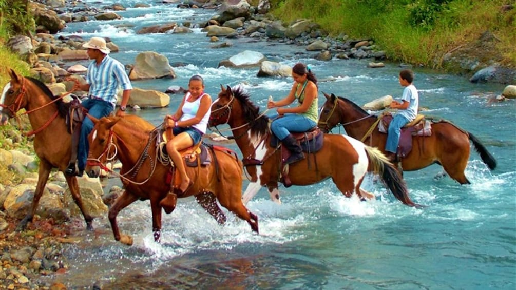Show item 2 of 4. Group riding horseback through a river in Costa rica