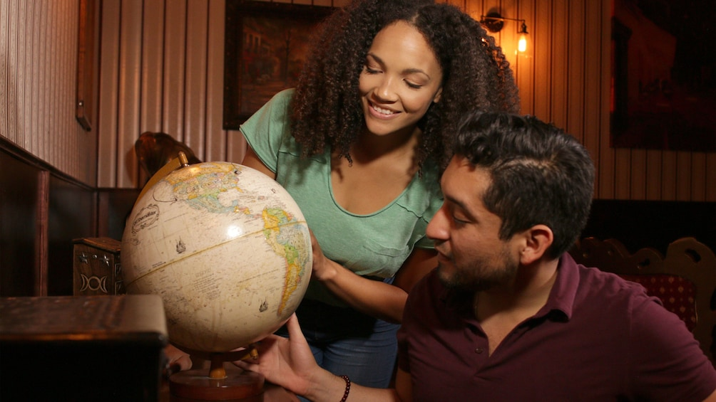 Show item 5 of 5. Couple consulting a globe during a game in Salt Lake Valley