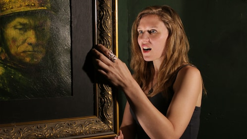 Woman looking behind a picture frame in a room escape game in Salt Lake Valley