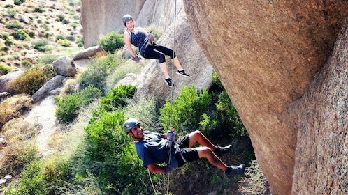 Couple rappelling down a cliff in Arizona
