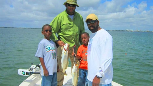 Two men and two boys hold fish they caught on a boat
