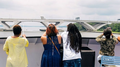 Passengers looking out at the sites from the deck of a cruise boat in Washington DC