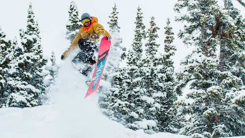 Young man making a jump on a snoaboard trip in Keystone