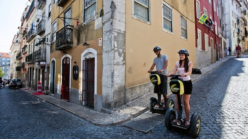 Couple riding segways through the old streets of Lisbon