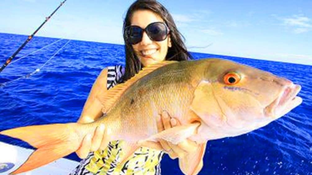 Show item 9 of 9. Woman holds a red snapper