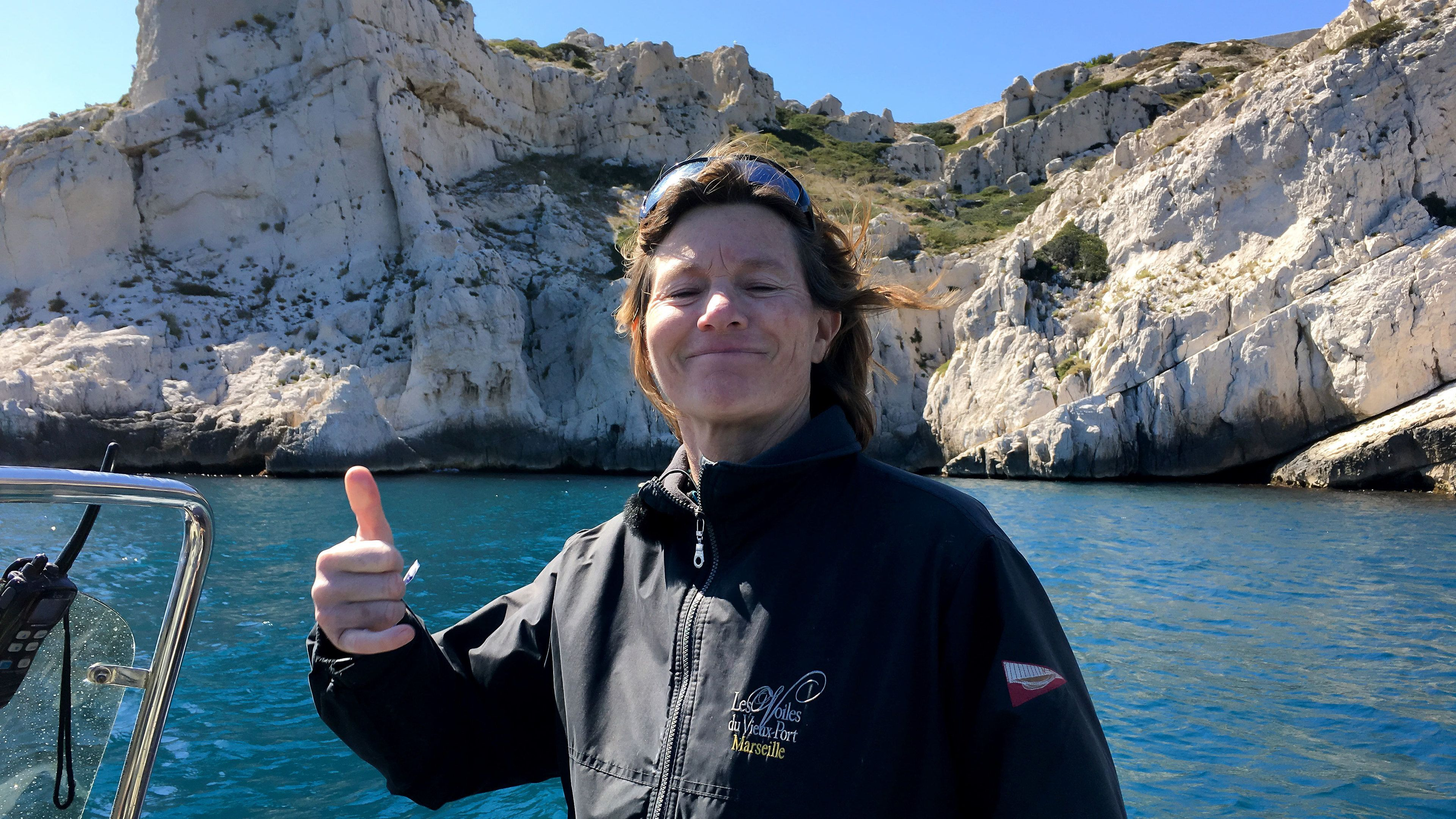 Woman giving thumbs up from a boat in the waters of the Marseille Calanques