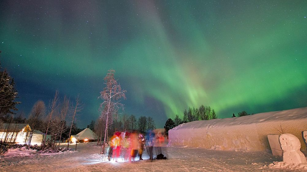people viewing northern lights in sky