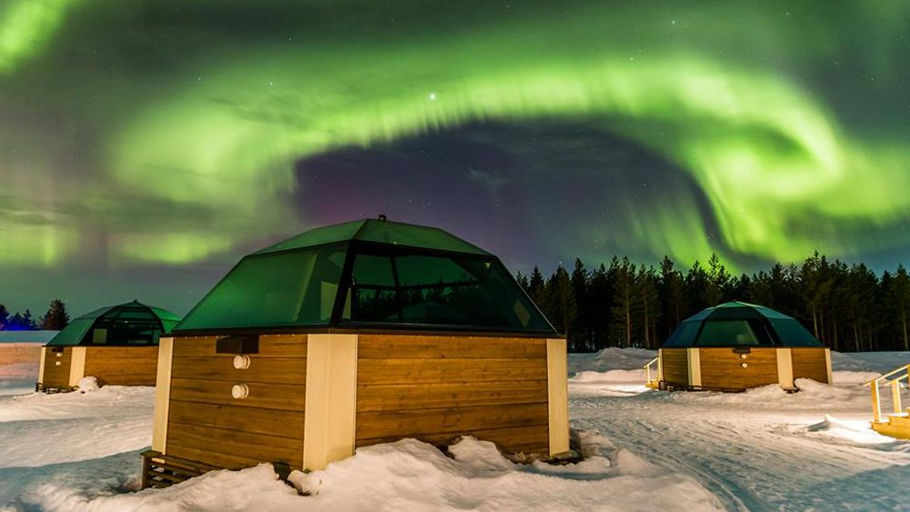 northern lights in sky above small buildings