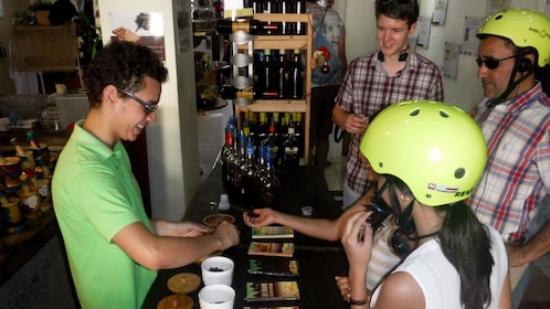 Bicycling group sampling food at a shop in Santo Domingo