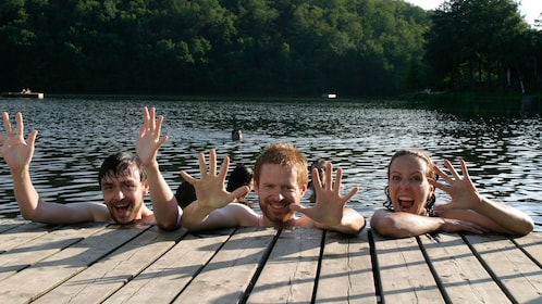 Three people swimming in a lake next to a dock