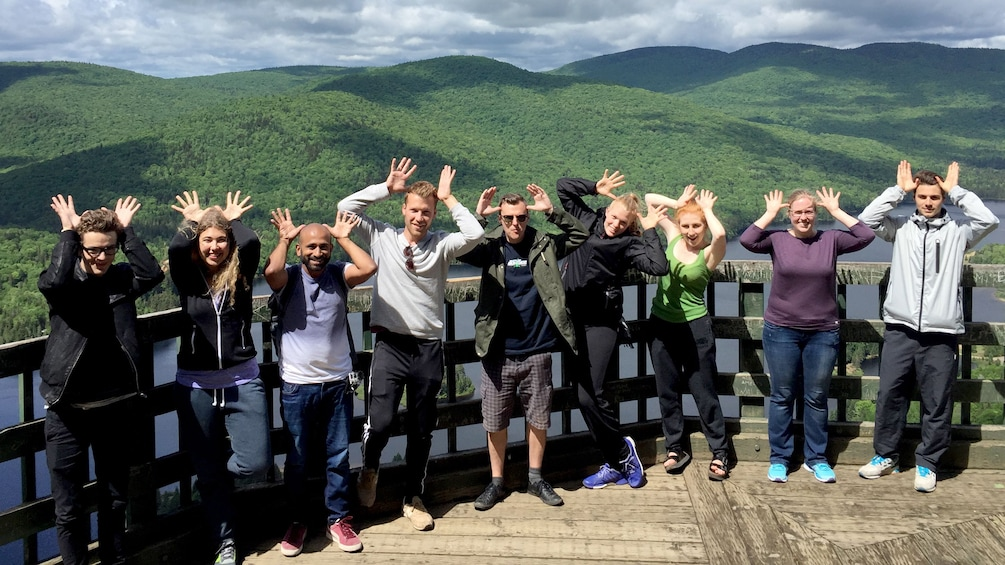 Show item 1 of 4. A tour group making moose  antlers with their hands in a scenic view point of Canadian hills
