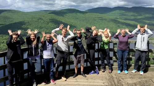 A tour group making moose antlers with their hands in a scenic view point of Canadian hills