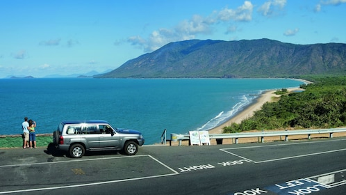 Couple pulled over to enjoy the view of the mountains and ocean in Cairns