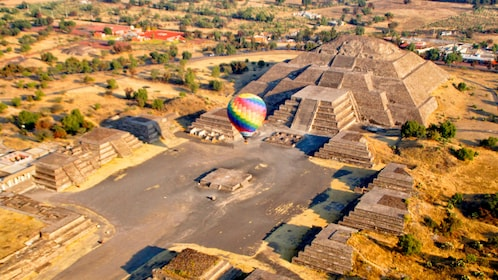 A Hot Air balloon hovering over a Mexican pyramid