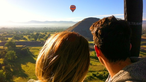 A couple looking out at a Hot Air balloon over a Mexican pyramid