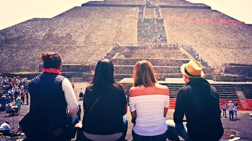 A group of people sit at the base of a Mexican pyramid