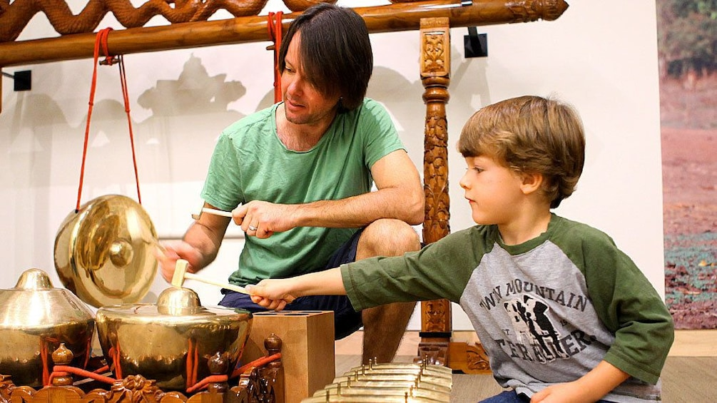 Show item 1 of 5. Father and son at an interactive exhibit at the Musical Instrument Museum in Phoenix