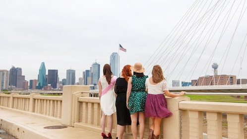 Group of women on a bridge looking at the city of Dallas