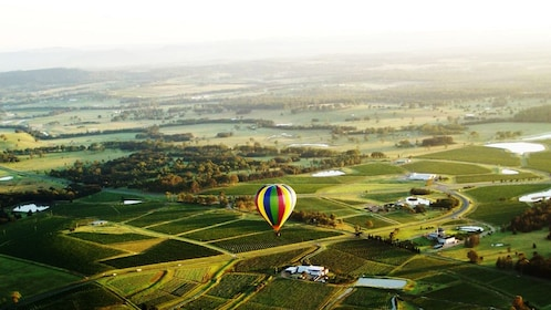 a hot air balloon floating high above landscape in Hunter Valley