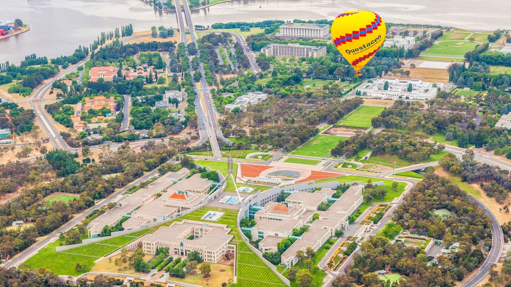 Show item 3 of 5. Aerial of yellow hot air balloon flying over Canberra.