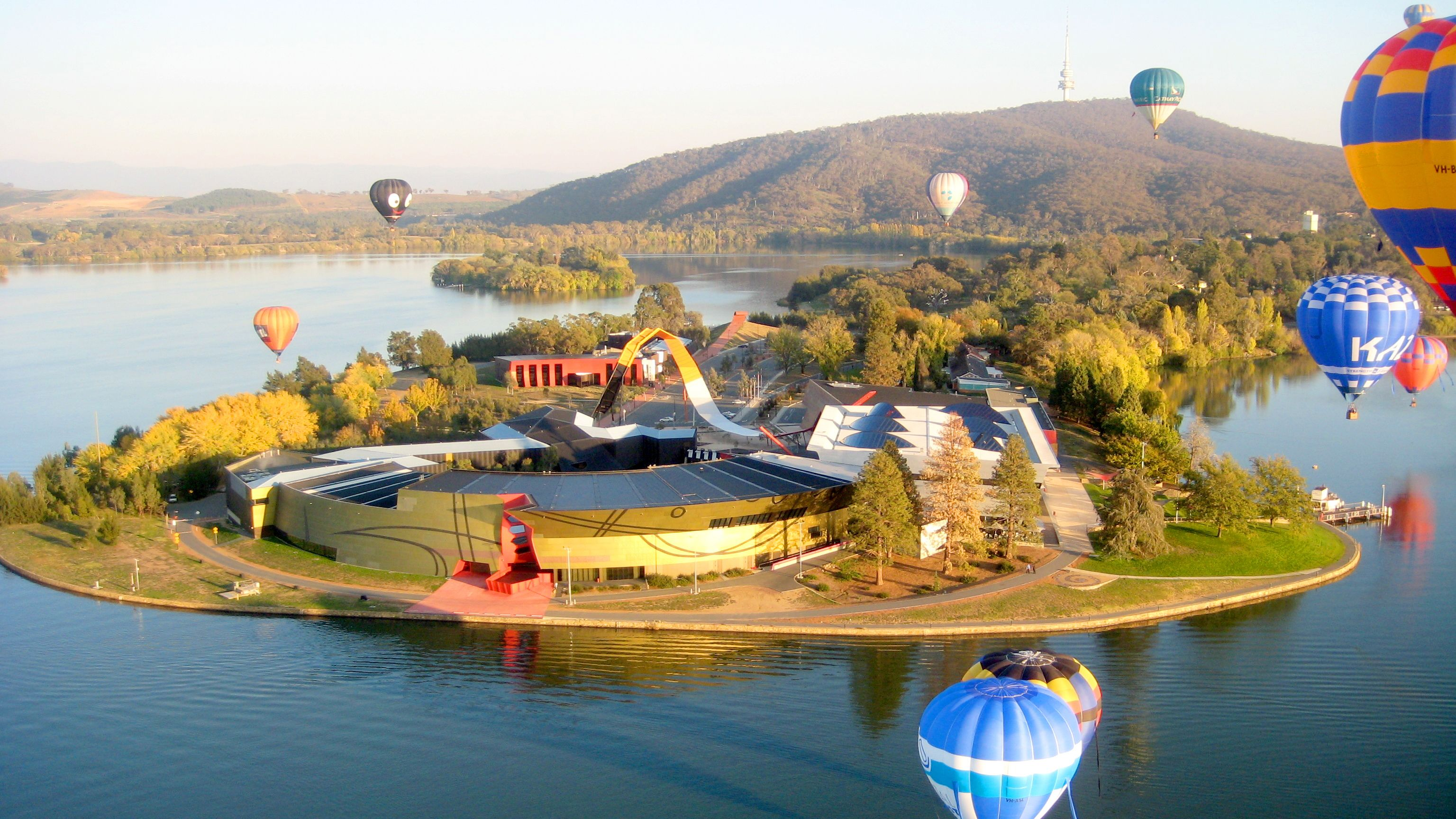 Hot air balloons flying around a peninsula near Canberra.
