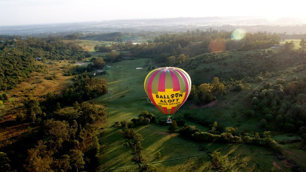 Show item 1 of 4. hot air ballon floats above landscape in Sydney