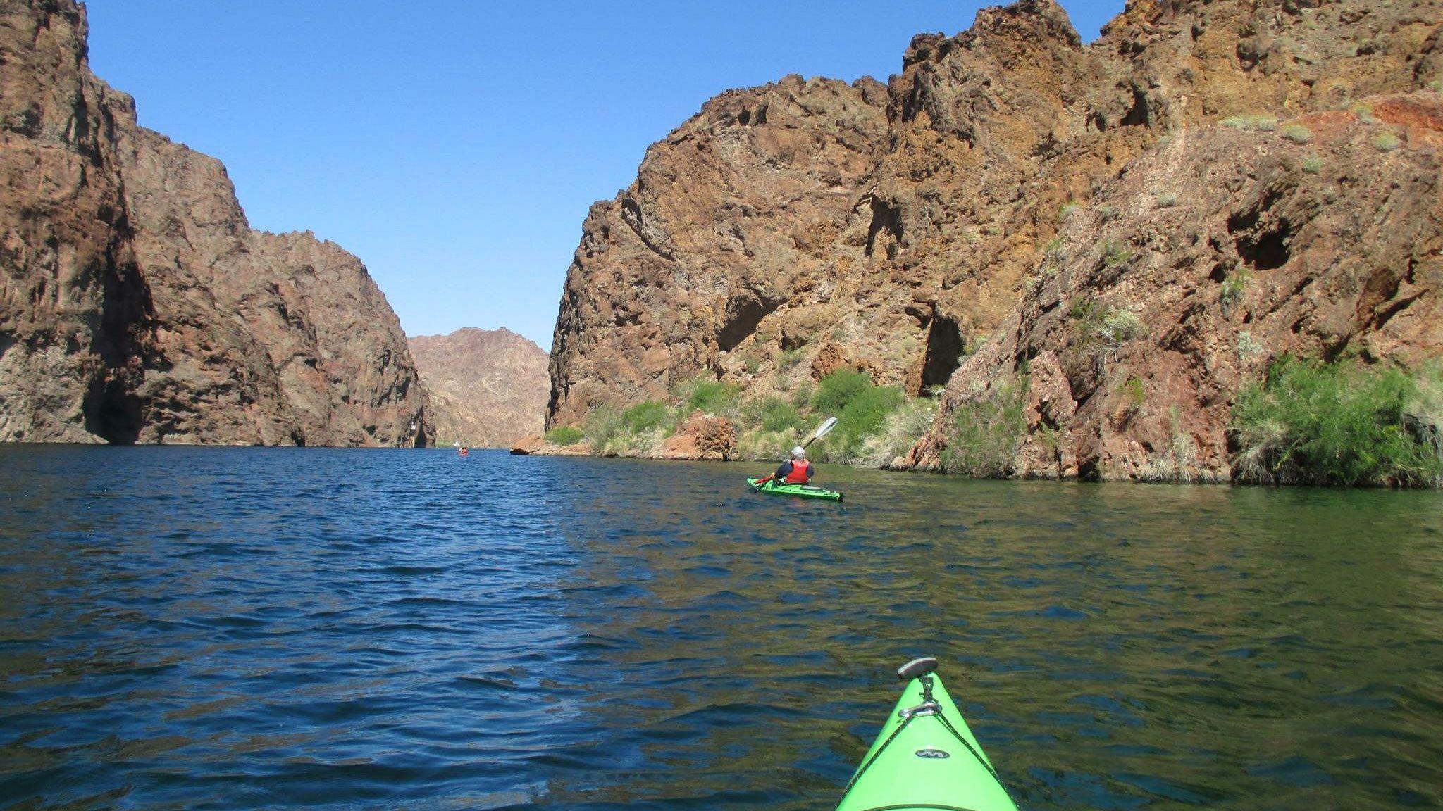 Two kayakers paddling down Colorado river