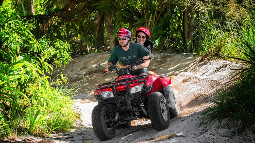 Show item 1 of 10. Two people on an ATV on a trail