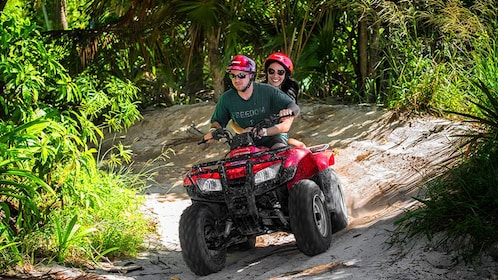 Two people on an ATV on a trail
