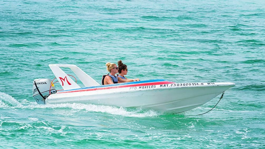 A speedboat of two people in Cancun
