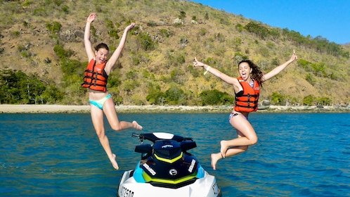 Pair of girls jumping off a jet ski in Whitsunday