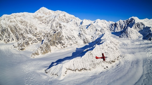 A red plane flies over a snowy mountain top in Alaska