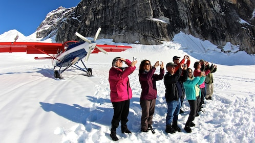 Tour group next to airplane on snowy mountain top