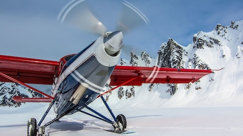 Red plane on a Mountain top covered in snow