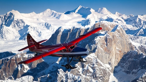 Red plane flying over the mountains in Alaska