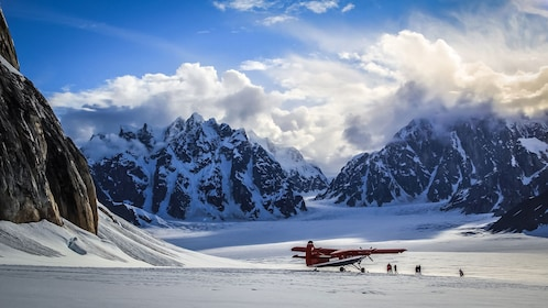 Tour group next to red plane on a snowy mountain top