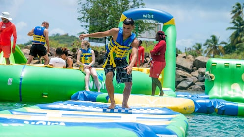 Young man running on a raft at a water park in St Lucia