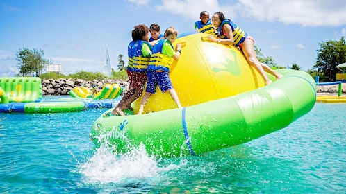 Kids playing on a raft in the water at Splash Island Water Park