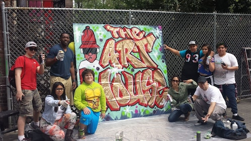 Young people stand next to a graffiti sign.