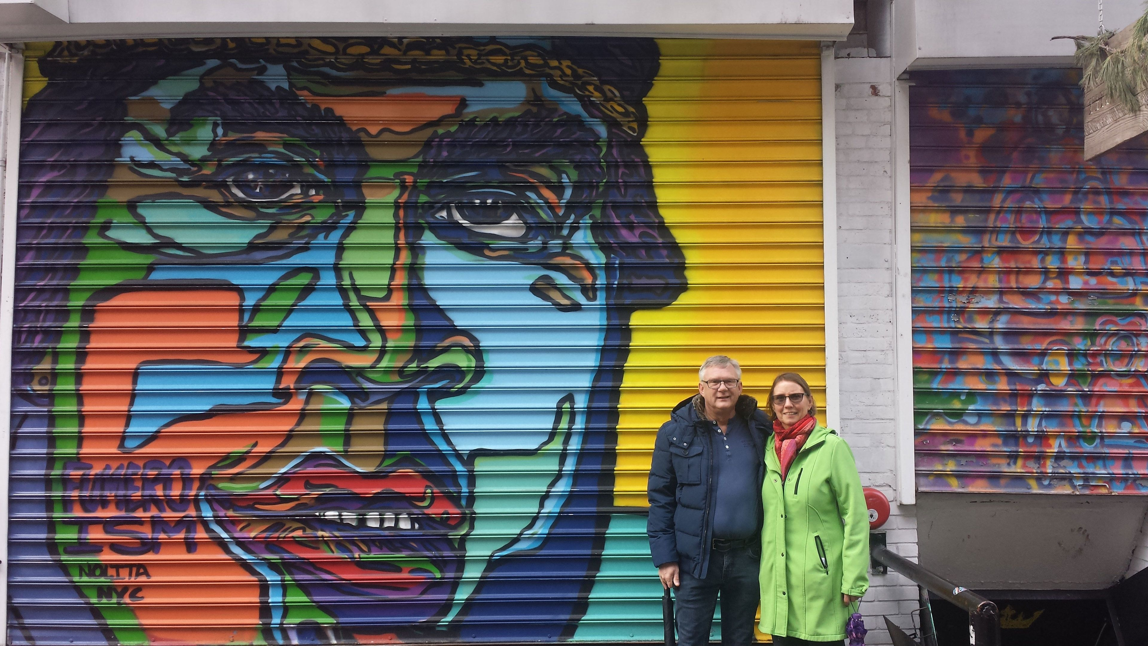 Two people stand next to Graffiti