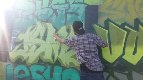 A young man spray painting graffiti