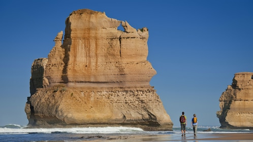 Two people walking on the beach next to the 12 Apostles in Melbourne